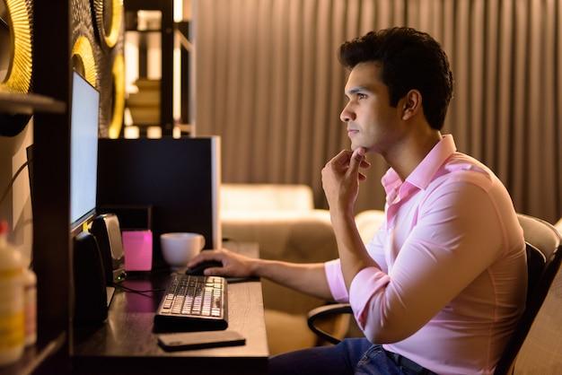 Joven empresario indio guapo pensando mientras trabaja horas extras en casa