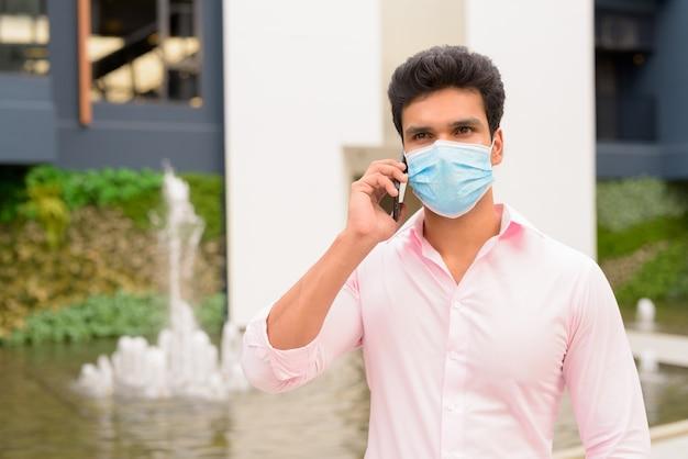 Joven empresario indio con máscara hablando por teléfono en la ciudad al aire libre