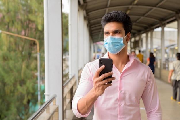 Joven empresario indio con máscara pensando mientras usa el teléfono en la pasarela