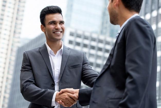 Joven empresario indio sonriente haciendo apretón de manos con pareja