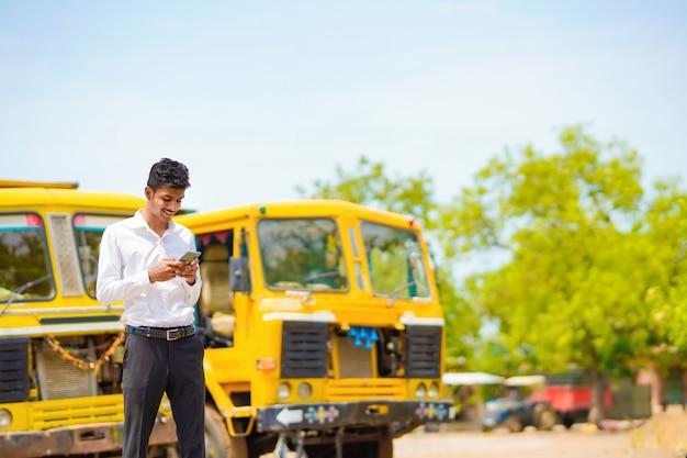 Joven empresario indio con su camión o camión de carga y hablando por teléfono inteligente.