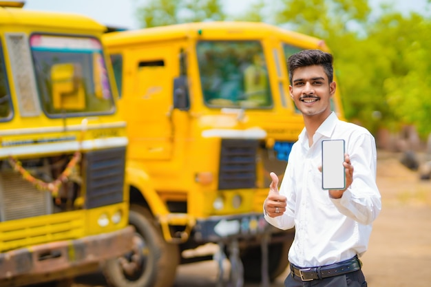 Joven empresario indio con su camión o camión de carga y mostrando el teléfono inteligente.