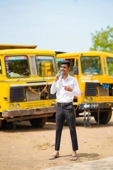 Joven empresario indio con su camión o camión de carga.