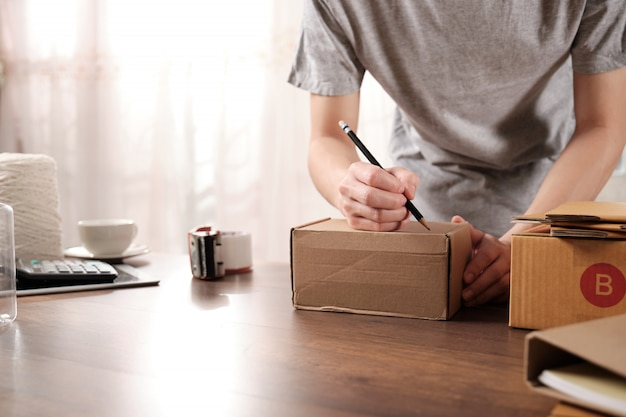 Joven empresario de inicio escribiendo la dirección en una caja de cartón en casa