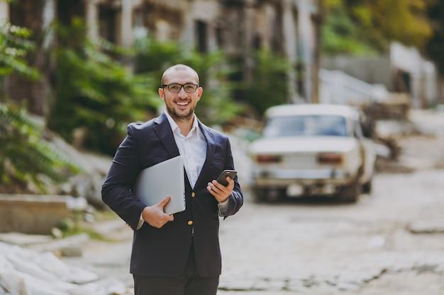 Joven empresario inteligente exitoso en camisa blanca, traje clásico, gafas. hombre de pie con el teléfono de la computadora del ordenador portátil cerca de las ruinas, escombros, edificio de piedra al aire libre. oficina móvil, negocio, concepto de trabajo.