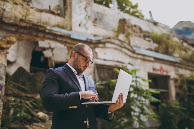 Joven empresario inteligente exitoso en camisa blanca, traje clásico, gafas. hombre de pie y trabajando en una computadora portátil cerca de ruinas, escombros, edificio de piedra al aire libre. oficina móvil, concepto de negocio.