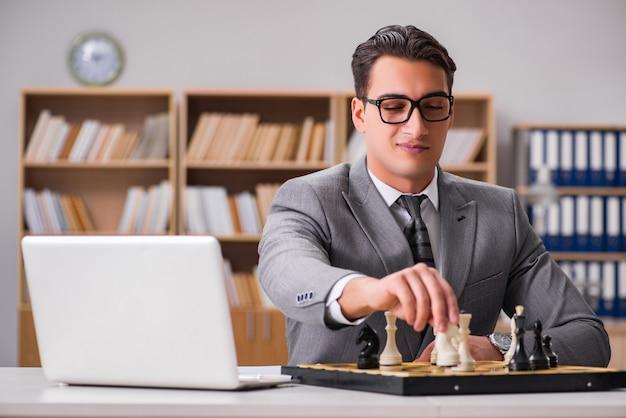 Joven empresario jugando al ajedrez en la oficina