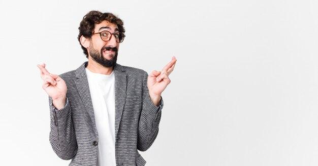 Joven empresario loco cruzando los dedos con ansiedad y esperando buena suerte con una mirada preocupada sobre la pared
