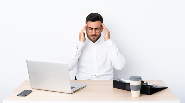 Joven empresario en un lugar de trabajo con dolor de cabeza