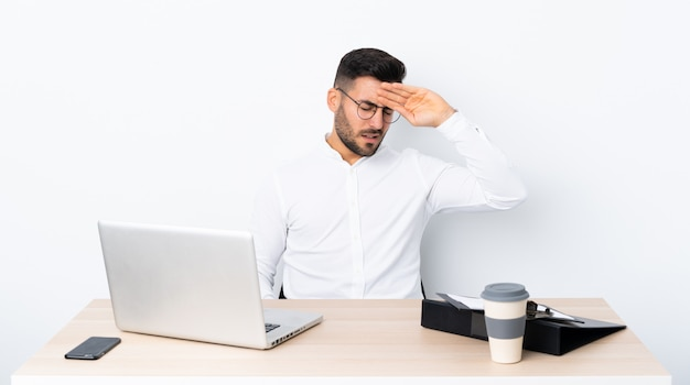 Joven empresario en un lugar de trabajo con expresión cansada y enferma