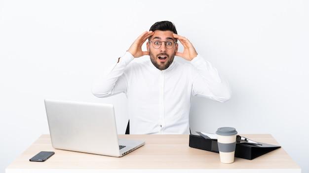 Joven empresario en un lugar de trabajo con expresión de sorpresa