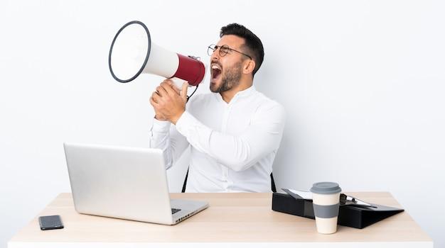 Joven empresario en un lugar de trabajo gritando a través de un megáfono