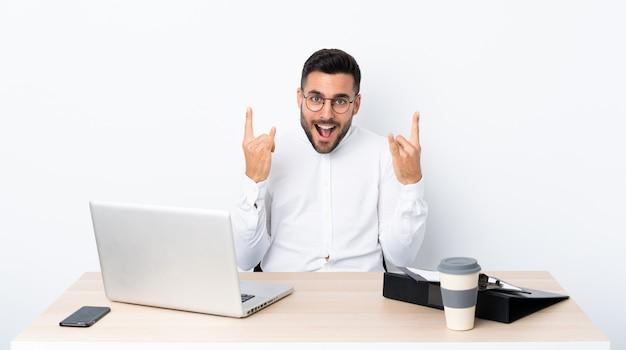 Joven empresario en un lugar de trabajo haciendo gesto de rock