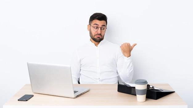 Joven empresario en un lugar de trabajo infeliz y apuntando hacia un lado