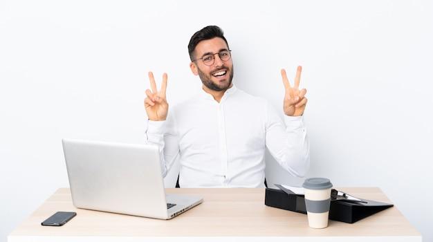 Joven empresario en un lugar de trabajo que muestra el signo de la victoria con ambas manos