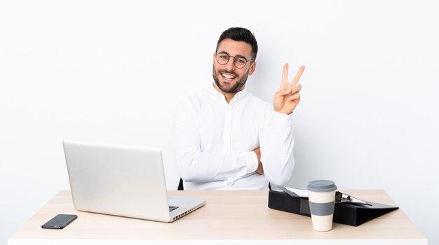 Joven empresario en un lugar de trabajo sonriendo y mostrando el signo de la victoria