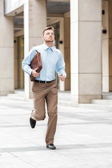 Joven empresario con un maletín corriendo en una calle de la ciudad. apresurándose a trabajar.