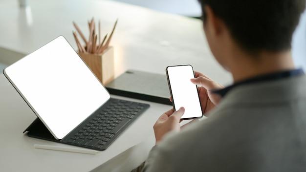 Joven empresario mantenga un teléfono inteligente de pantalla en blanco en la mano y un portátil de pantalla en blanco en el escritorio.