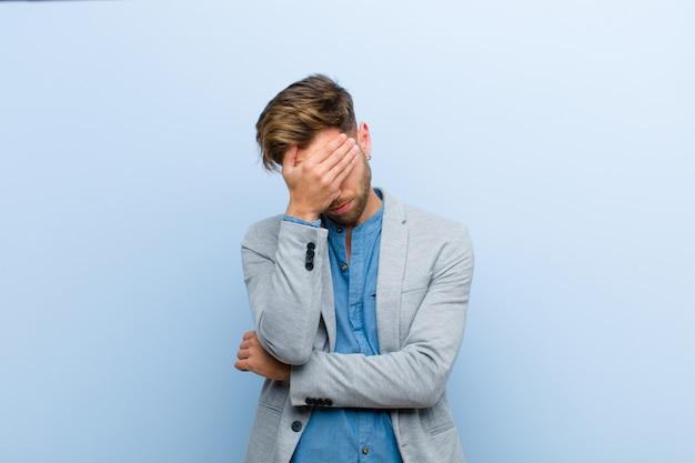 Joven empresario mirando estresado, avergonzado o molesto, con dolor de cabeza, cubriéndose la cara con la mano contra el azul