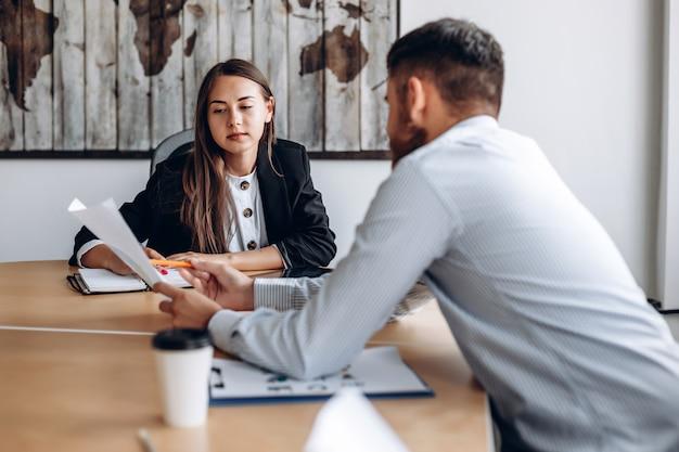 Joven empresario muestra los resultados del trabajo a su gerente. trabajar en la oficina