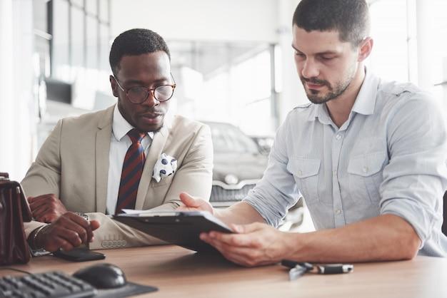 Un joven empresario negro atractivo compra un auto nuevo, firma un contrato y lleva las llaves al gerente