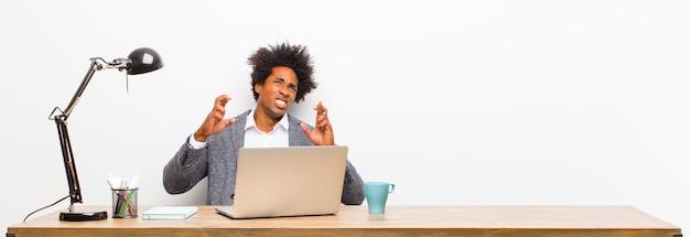 Joven empresario negro cruzando los dedos con ansiedad y esperando buena suerte con una mirada preocupada en un escritorio