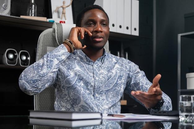 Joven empresario negro hablando teléfono móvil sentado en la computadora de escritorio en la oficina