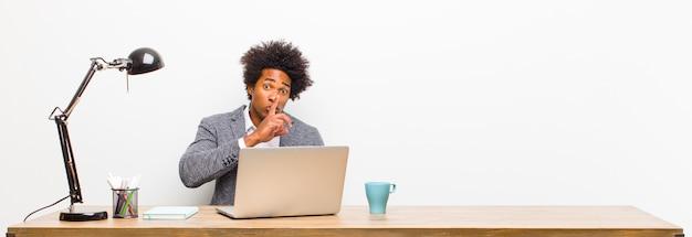 Joven empresario negro pidiendo silencio y silencio, gesticulando con el dedo frente a la boca, diciendo shh o guardando un secreto en un escritorio