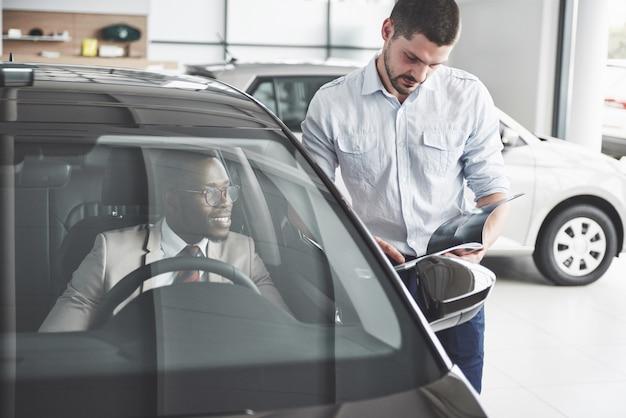 Joven empresario negro prueba conducir coche nuevo. rico hombre afroamericano