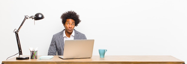Joven empresario negro que parece tonto y divertido con una expresión tonta, bromeando y bromeando en un escritorio