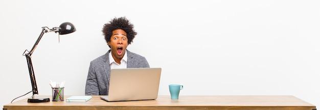 Joven empresario negro sintiéndose aterrorizado y conmocionado, con la boca abierta de sorpresa en un escritorio