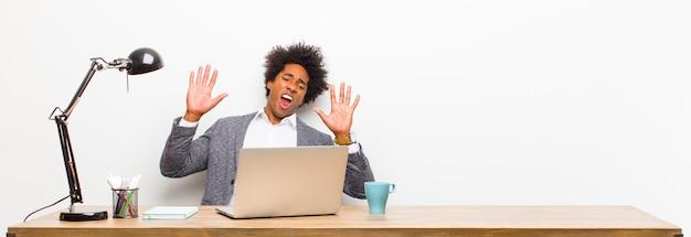 Joven empresario negro sintiéndose estupefacto y asustado