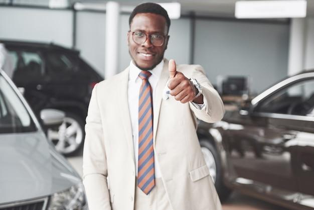 Joven empresario negro sobre fondo de salón de auto. venta de coches y concepto de alquiler