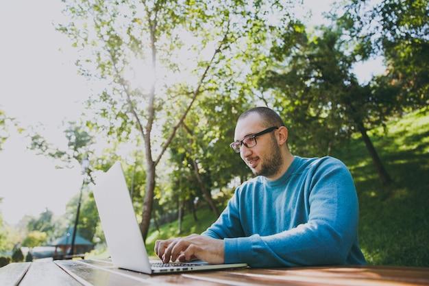 Joven empresario o estudiante inteligente exitoso en gafas de camisa azul casual sentado en la mesa con el teléfono móvil en el parque de la ciudad usando la computadora portátil trabajando al aire libre en la naturaleza verde. concepto de oficina móvil.