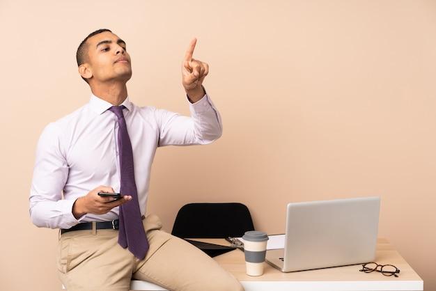 Joven empresario en una oficina tocando en pantalla transparente