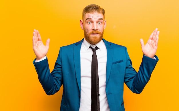 Joven empresario pelirrojo que parece sorprendido y asombrado, con la boca abierta de sorpresa al darse cuenta de algo increíble contra naranja