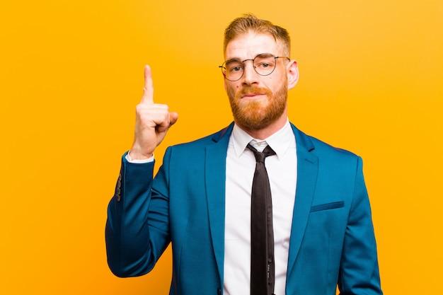Joven empresario pelirrojo que se siente como un genio sosteniendo el dedo con orgullo en el aire después de darse cuenta de una gran idea, diciendo eureka orange wall
