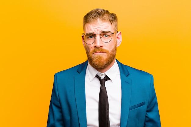 Joven empresario pelirrojo sintiéndose confundido y dudoso, preguntándose o tratando de elegir o tomar una decisión contra naranja