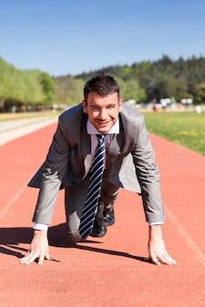 Joven empresario en una pista de atletismo en verano