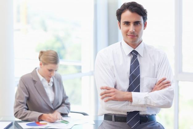 Joven empresario posando mientras su colega está trabajando