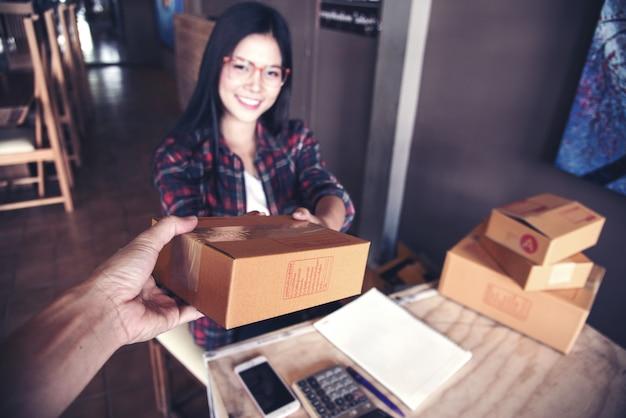 Joven empresario, propietario de un negocio adolescente, trabajo en casa, caja para entrega