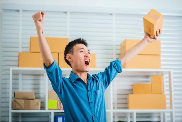 Joven empresario pyme con caja sintiéndose feliz.
