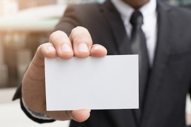Joven empresario que saca una tarjeta de presentación en blanco del bolsillo