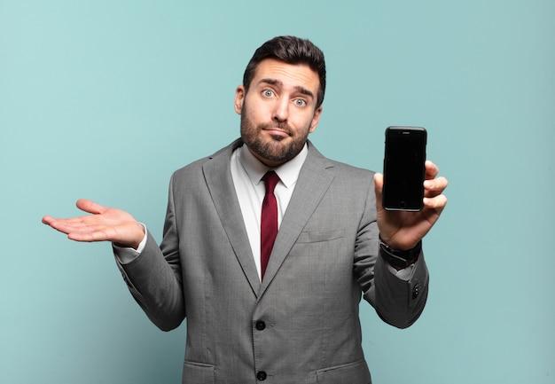 Joven empresario que se siente desconcertado y confundido, dudando, ponderando o eligiendo diferentes opciones con expresión divertida y mostrando la pantalla de su teléfono