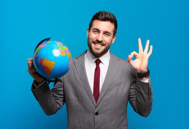Joven empresario que se siente feliz, relajado y satisfecho, mostrando aprobación con un gesto aceptable, sonriendo sosteniendo un mapa del globo terráqueo