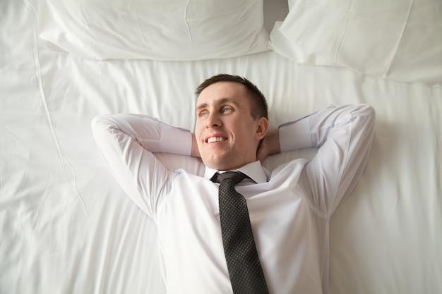 Joven empresario relajarse en la cama