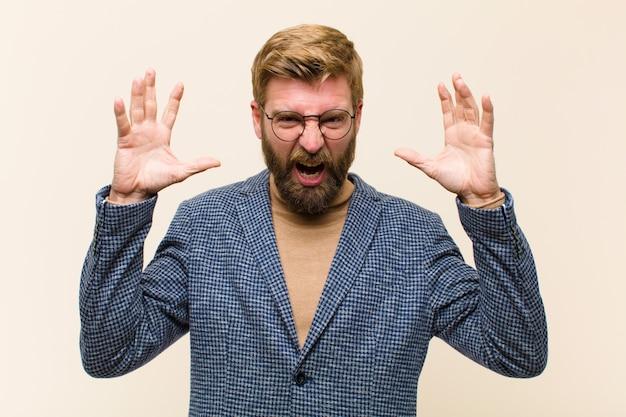 Joven empresario rubio gritando de pánico o ira, sorprendido, aterrorizado o furioso, con las manos al lado de la cabeza