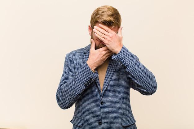 Joven empresario rubio que cubre la cara con ambas manos diciendo no a la cámara! rechazar fotos o prohibir fotos