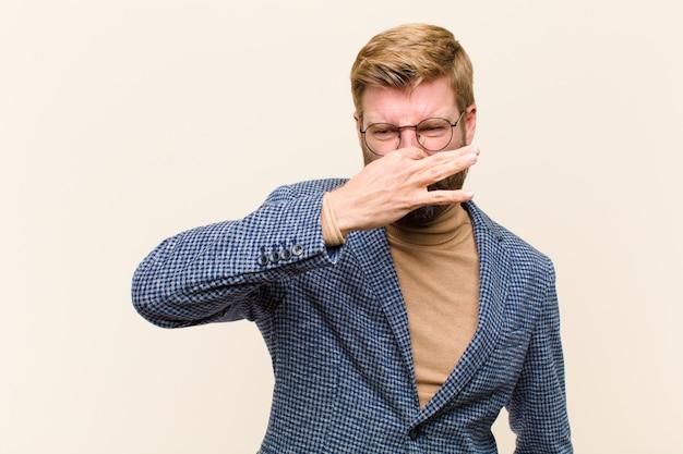 Joven empresario rubio se siente disgustado con la nariz para evitar oler un hedor desagradable y desagradable