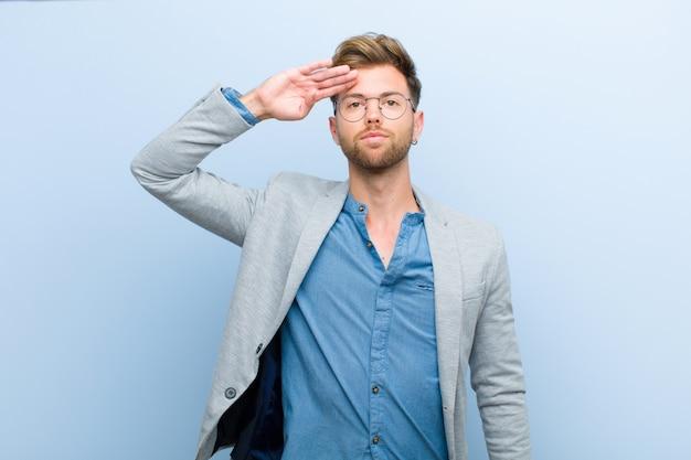 Joven empresario saludando a la cámara con un saludo militar en un acto de honor y patriotismo, mostrando respeto por la pared azul